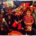 "Joshua (in the center in red and black) with friends in his bedroom doing ""Beyblades"""